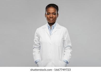 concept de médecine, de profession et de soins de santé - souriante afro-américaine docteur ou scientifique en blouse blanche sur fond gris