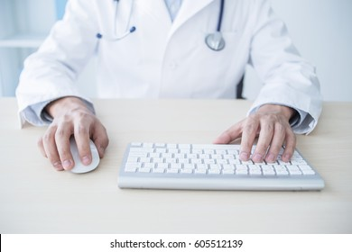 medicine, profession, technology and people concept - smiling male doctor with laptop in medical office
