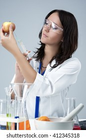 Medicine and Science Concepts. Caucasian Female Researcher Making Test Injection To the Fruits in laboratory. Vertical Image Composition