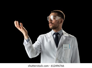 medicine, science, healthcare and people concept - male doctor or scientist in white coat and safety glasses touching something invisible over black background
