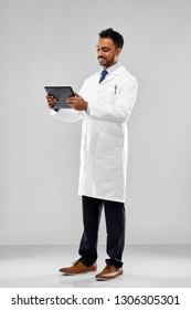 medicine, science and profession concept - smiling indian male doctor or scientist in white coat with tablet computer over grey background
