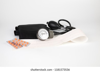 Medicine: sphygmomanometer, electrocardiogram (ECG), pills and blisters pack on a white background.