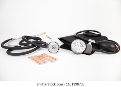Medicine: sphygmomanometer, stethoscope, pills and blisters pack on a white background.