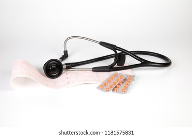 Medicine: stethoscope, electrocardiogram (ECG), pills and blisters pack on a white background.