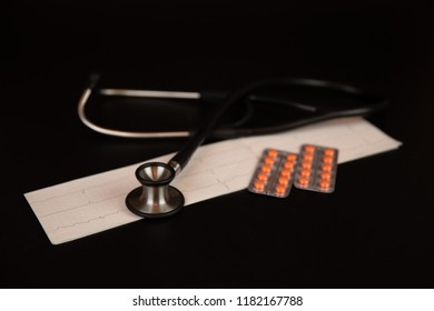 Medicine: stethoscope, electrocardiogram (ECG), pills and blisters pack on a black background.