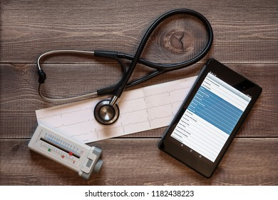 Medicine: stethoscope, peak flow meter, and tablet computer on a wooden background.