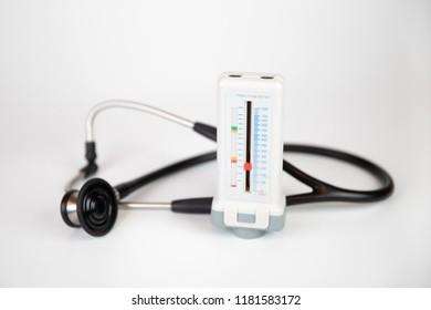 Medicine: stethoscope and peak flow meteron a white background.