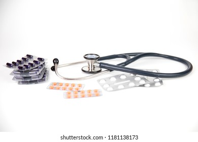 Medicine: stethoscope, pills and blisters pack on a white background.