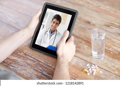 medicine, technology and healthcare concept - close up of patient with pills and water on table having video chat with doctor on tablet pc computer