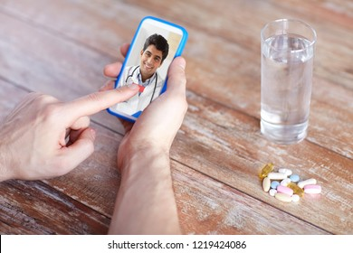medicine, technology and healthcare concept - close up of patient with pills and water on table having video chat with doctor on smartphone