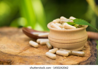 Medicine treatment herbal pills capsule on a wood stump in forest. Nature organic health care.