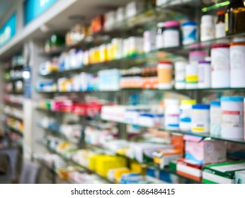 Medicines arranged on shelves in the pharmacy with blurred background.