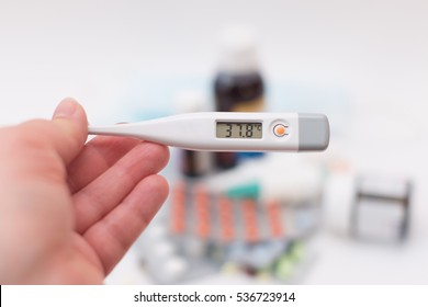 Medicines and a thermometer on white background. Seasonal flu or a cold.