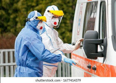 Medics with protective suits stand near ambulance for Coronavirus test.