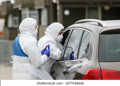 Medics with protective suits testing pacient for Coronavirus from car. COVID-19 outbreak.