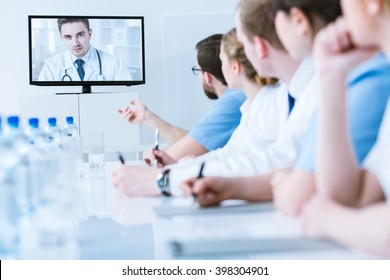 Medics in uniforms during video chat with young, handsome doctor, sitting in light office