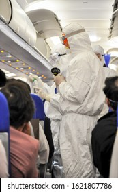 Medics in white hazmat protective suits checking and scanning passengers in a plane for epidemic virus symptoms. Chinese new Wuhan coronavirus illustration.