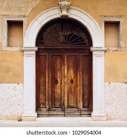 Medieval, ancient or vintage wooden door with ornate pattern and white stone arch columns. Front view, facade with yellow or light orange walls. Europe, Italy, Verona