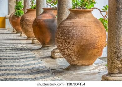 Medieval arcade view with orange ceramic vases and antique granite columns in Obidos, Portugal