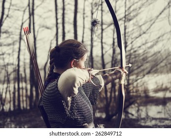 Medieval archer woman, she wearing a chainmail and use a bow and arrow, gloomy forest, cross-processed image.