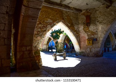 Medieval archway leading into the main square of the bastide town of Monpazier in the Dordogne region of France