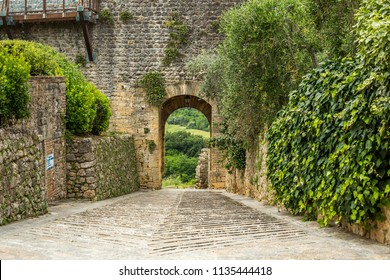 Medieval Archway in Stone Brick Wall with Cobblestone Road Looking Out into Countryside