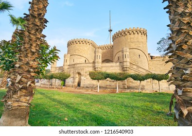 The medieval Bab Al-Azab Gate of the outer wall of Saladin Citadel with huge twin towers, massive porch and small guard towers, surrounded by ornamental garden, Cairo, Egypt.