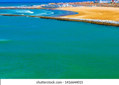The medieval bastion of Kasbah of the Udayas with two small turrets and the breakwaters that separate the Bou Regreg river mouth from the Atlantic Ocean on a sunny morning. Rabat, Morocco.
