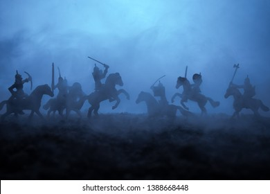 Medieval battle scene with cavalry and infantry. Silhouettes of figures as separate objects, fight between warriors on sunset foggy background. Artwork decoration. Selective focus
