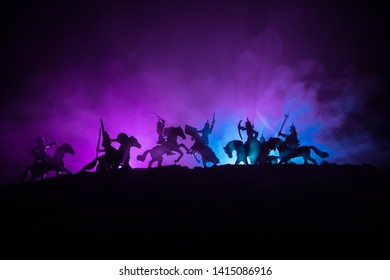 Medieval battle scene with cavalry and infantry. Silhouettes of figures as separate objects, fight between warriors on dark toned foggy background with medieval castle. Selective focus
