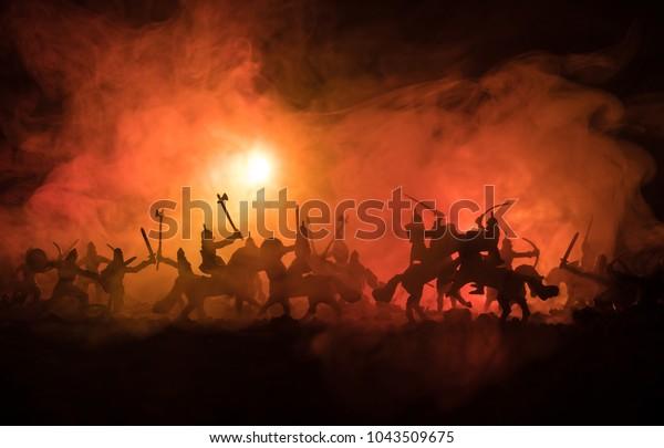 Средневековая сцена битвы с кавалерией и пехотой. Силуэты фигур как отдельные объекты, сражения между воинами на темном тонизированного туманного фона. Ночная сцена. Селективный фокус