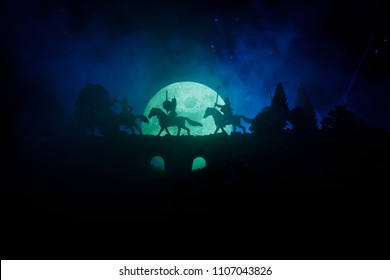 Medieval battle scene on bridge with cavalry and infantry. Silhouettes of figures as separate objects, fight between warriors on dark toned foggy background. Night scene. Selective focus