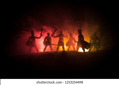Medieval battle scene. Silhouettes of figures as separate objects, fight between warriors on dark toned foggy background. Night scene. Selective focus