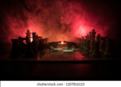 Medieval battle scene with two cannon on chessboard. Chess board game concept of business ideas and competition and strategy ideas Chess figures on a dark background with smoke and fog.