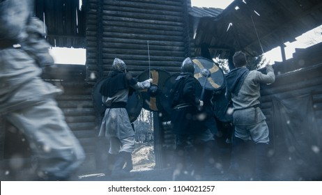 Medieval Battle. Viking Warriors Break into Wooden Fortress Yard and Fight with Slavs Guards. Violent Fight with Swords, Axes and Shields. Slow Motion. Medieval Reenactment.
