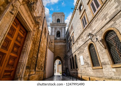 A medieval bell tower with a tunnel opens up to the ancient Piazza del duomo in the historic center of Brindisi Italy.