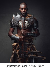 Medieval black skinned warrior with axes staring at camera in dark background