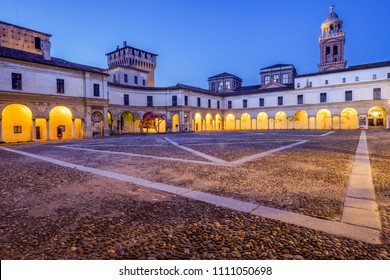 Medieval building inner court illuminated with yellow lights against blue sky early in the morning. Piazza Castello, Mantua, Italy. June 10, 2018