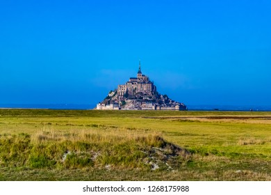 Medieval castle, against the blue sky and white clouds, the castle on the island, the castle is surrounded by water, green grass, a fortress and abbey, an incredibly beautiful castle like  fairy tale