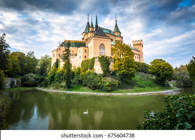 Medieval castle Bojnice over lake with swan. Dramatic illuminated blue sky with clouds. Central Europe, Slovakia.