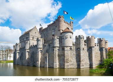 Medieval castle Gravensteen - Castle of the Counts with small windows surrounded by water in moat in Ghent, Flanders, Belgium.