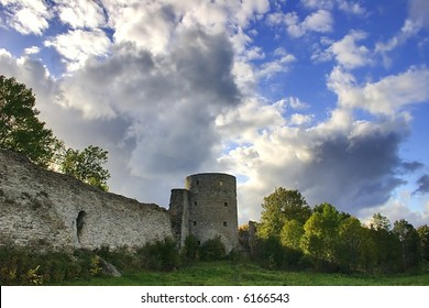 medieval castle and green trees under blue sky with clouds