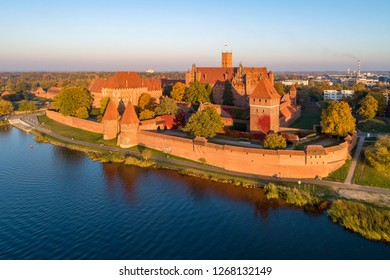 Medieval castle in Malbork, Poland, main fortress of the teutonic knights at the Nogat river. Aerial view in fall in sunset light.