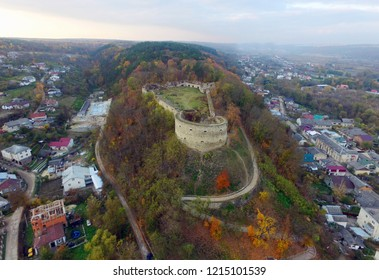 Medieval castle on mountain in old town Terebovlia in Ternopil region, Western Ukraine, on gloomy autumn day, aerial view. Mighty ruins of the fortress rise above the city. Architectural heritage.