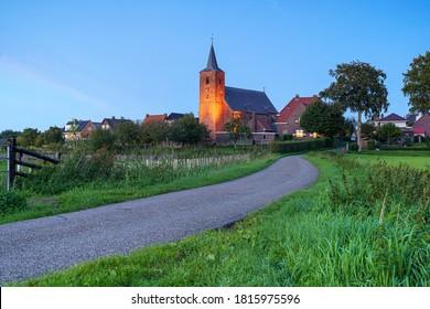 Medieval church in the floodplains on a dike of a Dutch river landscape
