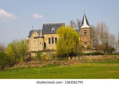 Medieval church and fortress on green hill in rural dutch landscape, Asselt near Venlo, Netherlands