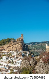 Medieval church on the edge of a dramatic cliff looking at the hills with oleve trees. The town of Montefrio at the side of the cliff.