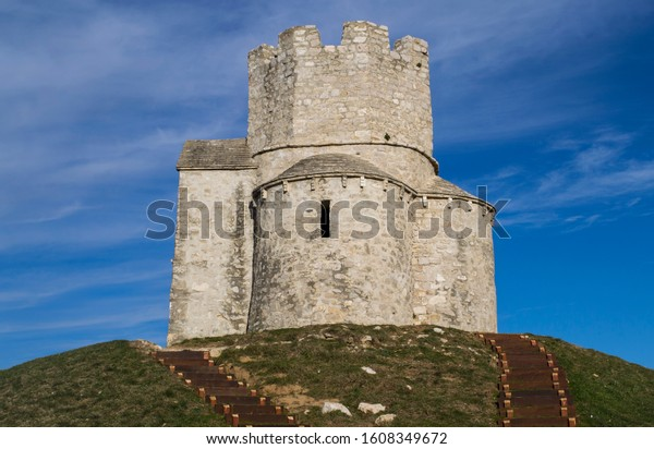 Medieval church of St. Nicholas built on ancient burial mound, sunny winter day