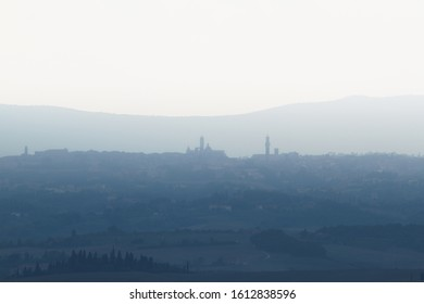 the medieval city of Siena, Tuscany, Italy. Distant Skyline. Artistic. Peaceful view from a hill, view from a distance. Blueish panorama. Fog. No clouds.