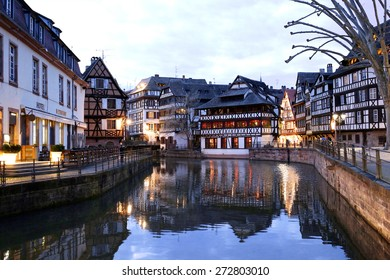 Medieval cityscape of Rhineland black and white timber-framed buildings in the Petite-France district alongside the river Ill at twilight - France, Alsace region, Strasbourg